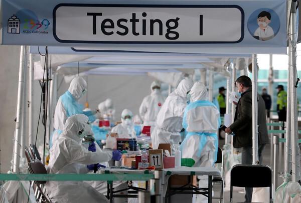 31일 오후 인천국제공항 제2터미널 옥외공간에 설치된 개방형 선별진료소(오픈 워킹스루)에서 런던 여객기를 타고 입국한 외국인들이 신종 코로나바이러스 감염증(코로나19)진단검사를 받고 있다. 인천국제공항 1,2 터미널에 각각 8개씩 설치된 개방형 선별진료소는 하루 최대 2천명 정도를 검사할 수 있다.2020.3.31/뉴스1