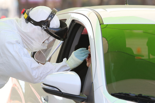 20일 오전 대구 수성구 대흥동 대구스타디움 P3 주차장에 마련된 차량선별진료소에서 수성구보건소 관계자들이 신종 코로나바이러스 감염증(코로나19) 의심 증상으로 방문한 시민의 검체를 채취하고 있다. 2020.3.20/뉴스1